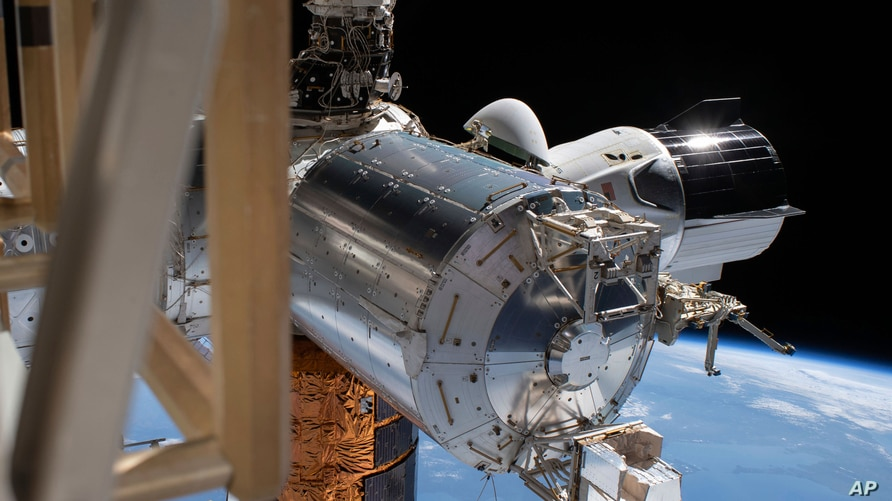 This July 1, 2020 photo made available by NASA shows the SpaceX Crew Dragon, right, docked to the International Space station,…