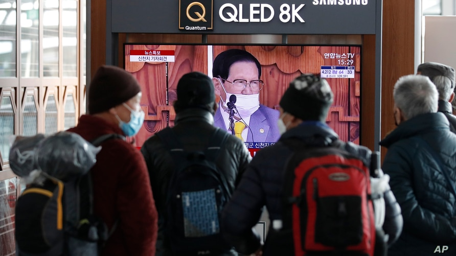 People watch a TV screen showing a live broadcast reporting about Lee Man-hee, a leader of Shincheonji Church of Jesus, at the…
