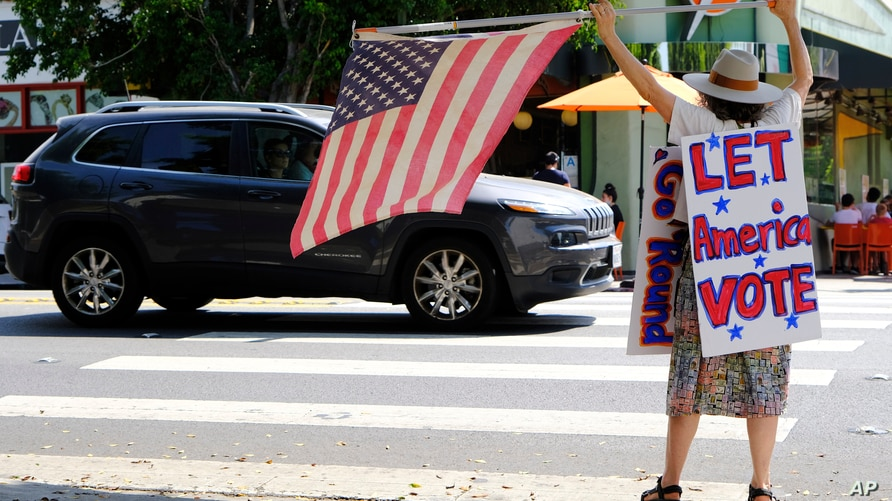 Erica Koesler of Los Angeles demonstrates in front of passing cars outside a USPS post office, Saturday, Aug. 15, 2020, in the…