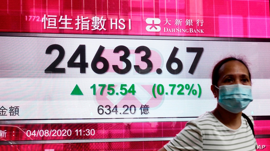 A woman wearing a face mask stands by a bank's electronic board showing the Hong Kong share index at Hong Kong Stock Exchange…