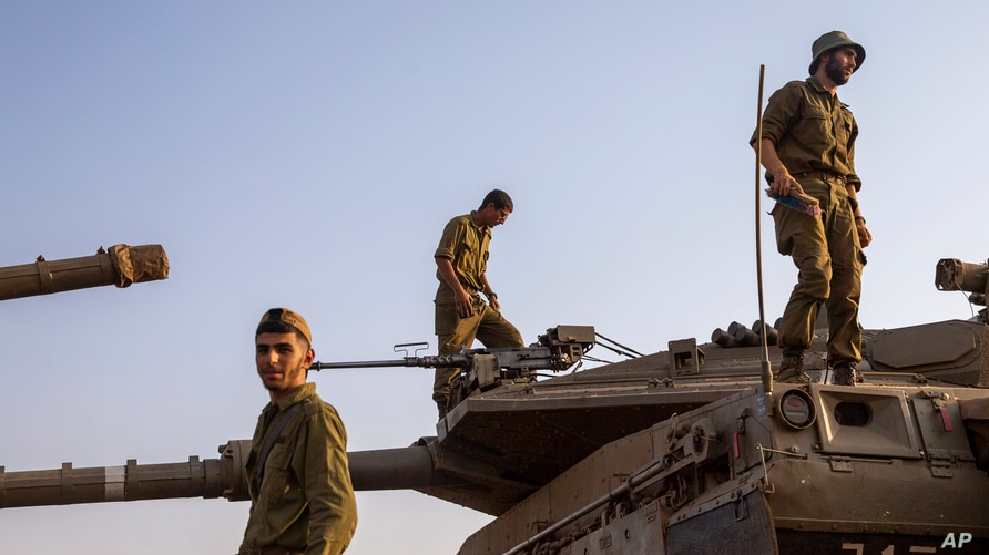 Israeli soldiers work on tanks in the Israeli controlled Golan Heights near the border with Syria, not far from Lebanon border,…