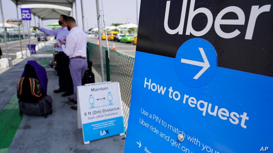 Travelers request an Uber ride at Los Angeles International Airport's LAX-it pick up terminal Thursday, Aug. 20, 2020. An…