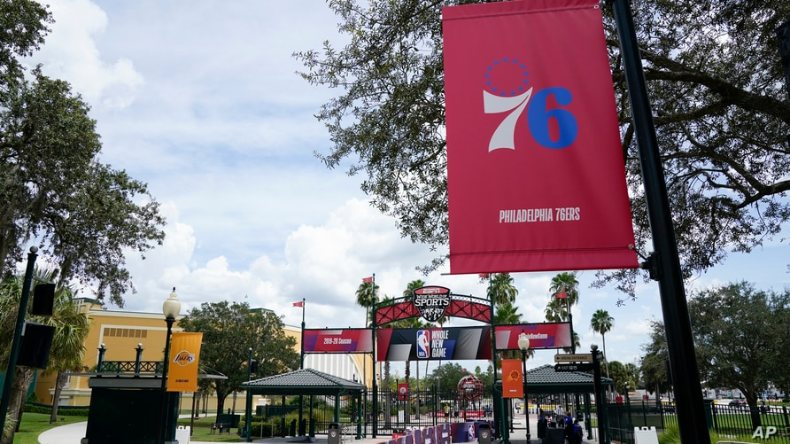 A Philadelphia 76ers banner, along with other NBA basketball team logos are displayed outside arenas Friday, Aug. 28, 2020, in…