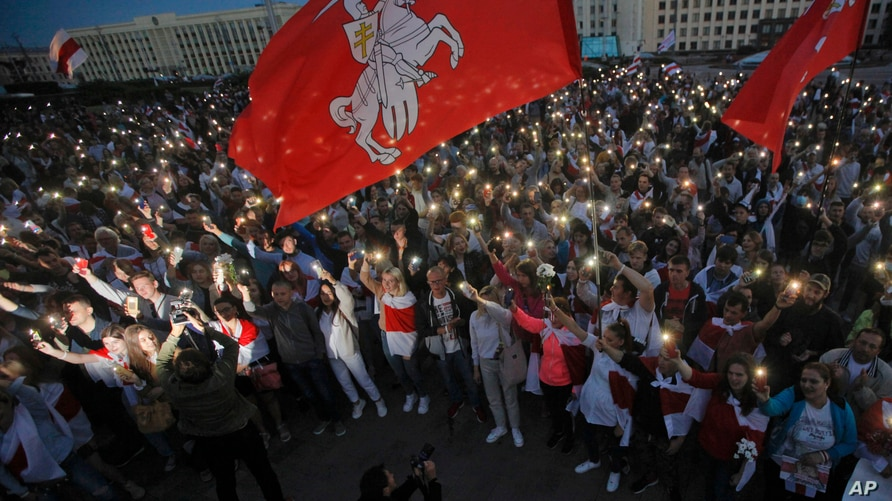 Belarusian opposition supporters light phones lights during a protest rally in front of the government building at Independence…
