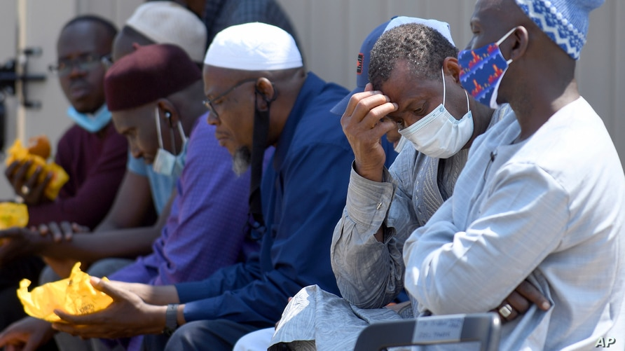 Men from West Africa sit near the site where five people were found dead after a house fire in suburban Denver, Wednesday, Aug…