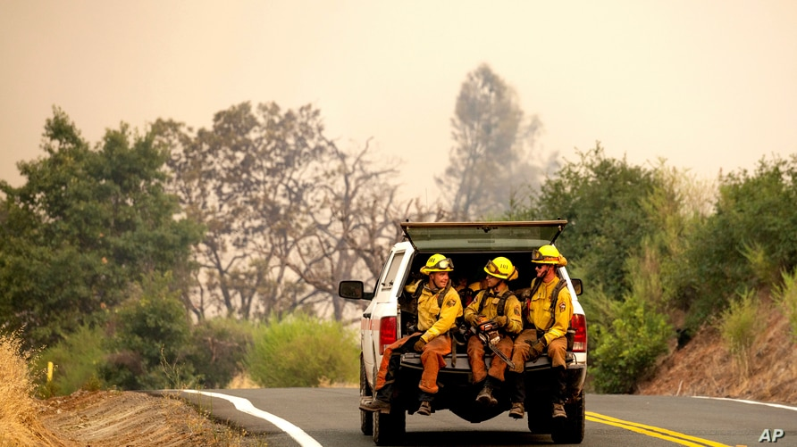 Firefighters ride in the back of a pickup truck while battling the LNU Lightning Complex fires Sunday, Aug. 23, 2020, in…