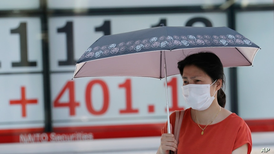 A woman wearing a face mask walks by an electronic stock board of a securities firm in Tokyo, Monday, Aug. 3, 2020. Asian…