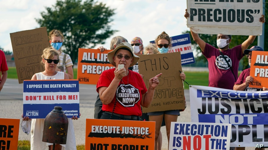 Sister Barbara Battista speaks to the crows of death penalty protestors gathered across the street from the federal prison…