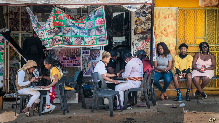 Customers have their nails done near the Baragwanath taxi rank in Soweto, South Africa, Wednesday Sept. 16, 2020. South African…