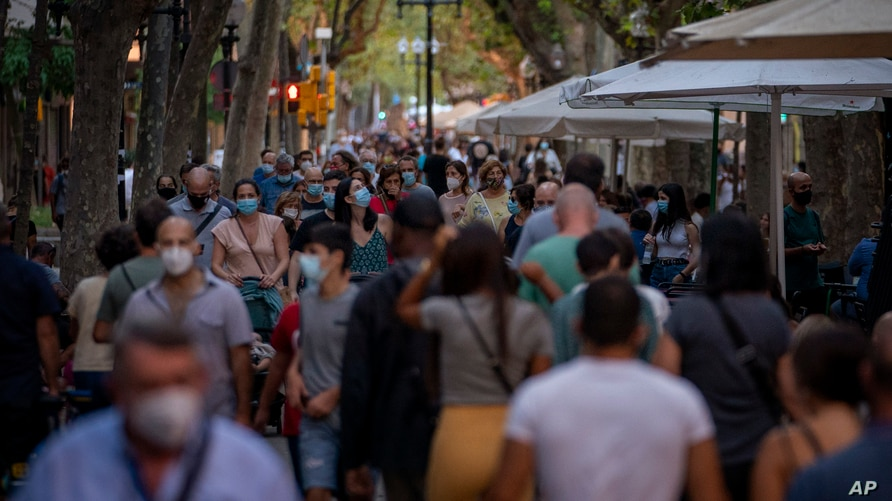 People wearing face masks walk along a boulevard in Barcelona, Spain on Sunday, Aug. 30, 2020. Spanish authorities have…