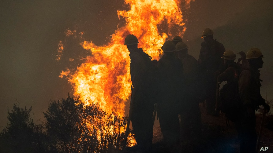 Firefighters monitor a controlled burn along Nacimiento-Fergusson Road to help contain the Dolan Fire near Big Sur, Calif.,…
