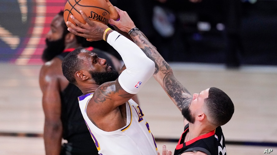Los Angeles Lakers' LeBron James, left, shoots over Houston Rockets' Austin Rivers during the second half of an NBA conference…