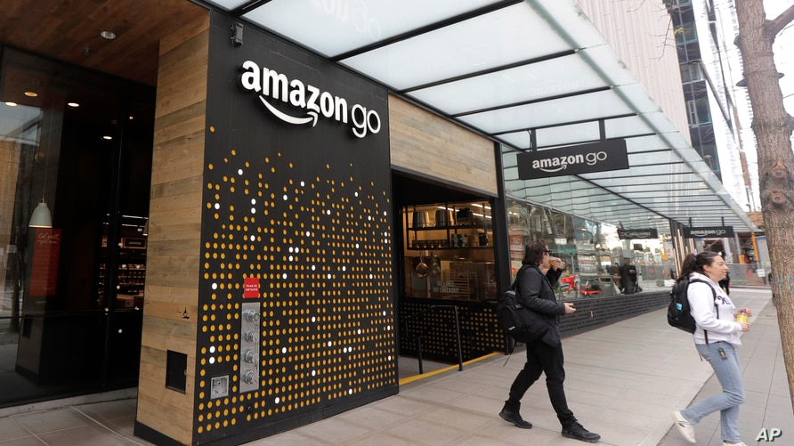 FILE - In this March 4, 2020 file photo, people walk out of an Amazon Go store, in Seattle. Amazon is rolling out a new device…