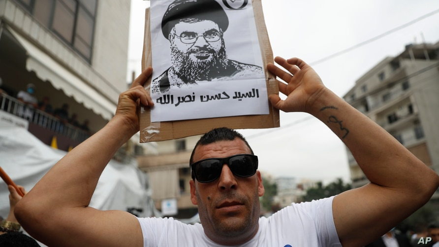 A Hezbollah supporter holds a placard depicting its leader Sayyed Hassan Nasrallah, during a protest against U.S. interference…