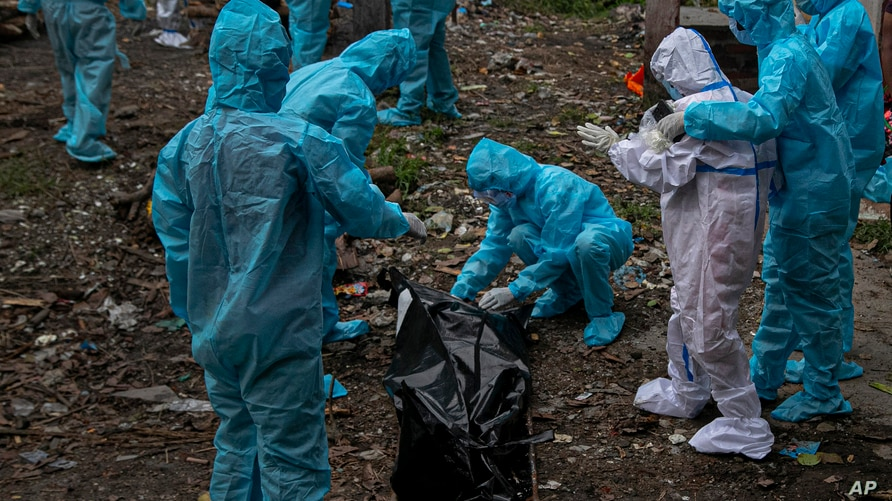 A woman, wearing white personnel protective equipment, reacts as she takes a glimpse of her husband's body, a victim of COVID…