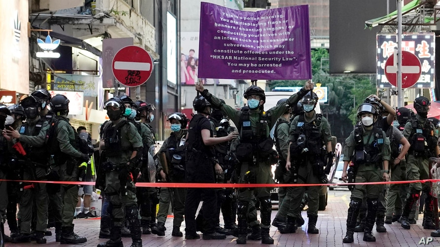 Police officers raise a warning banner at a downtown street in Hong Kong Sunday, Sept. 6, 2020. About 30 people were arrested…