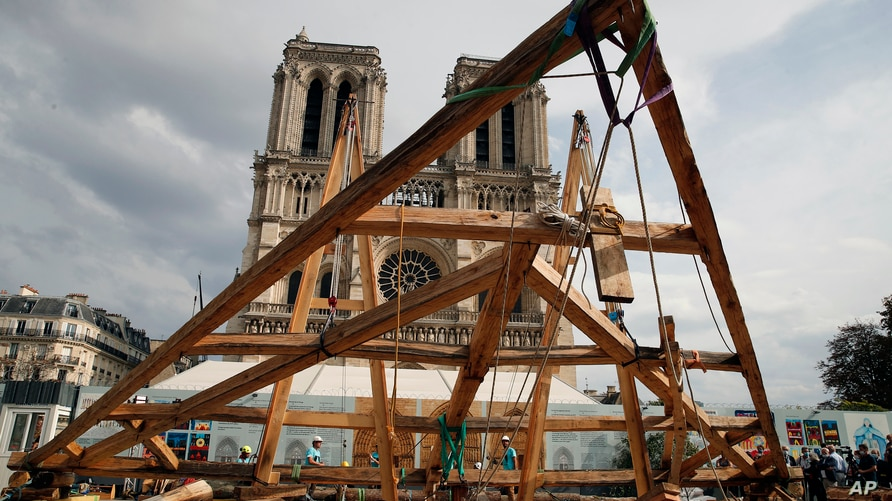 Carpenters put the skills of their Medieval colleagues on show on the plaza in front of Notre Dame Cathedral in Paris, France,…