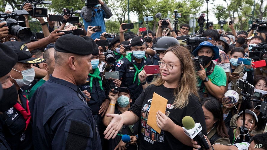 One of the pro-democracy student leaders negotiates with police officials as they march on road during a protest in Bangkok,…