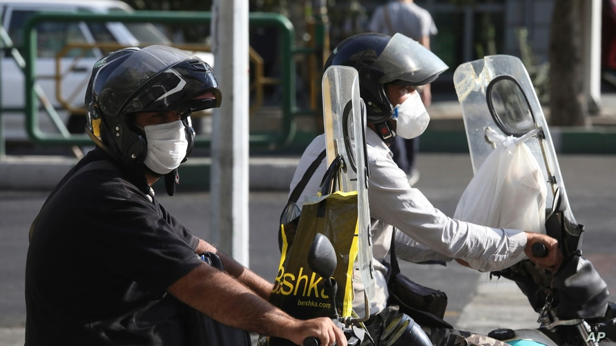 People on their motorcycles wearing protective face masks to help prevent the spread of the coronavirus wait for a green light…