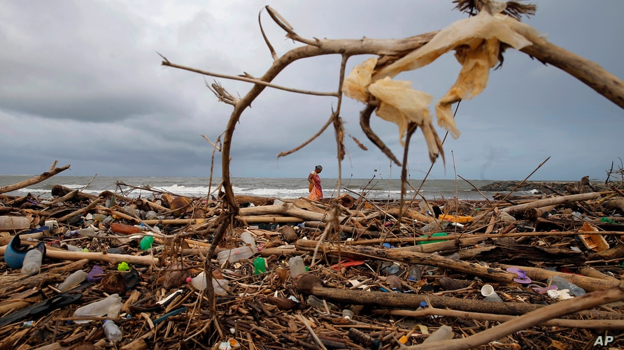 A Sri Lankan ragpicker searches for plastic waste washed ashore on the promenade of the Indian ocean in Colombo, Sri Lanka,…