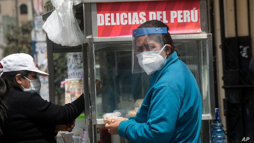 A woman wearing a mask and face shield buys a sandwich at a stand near the Clinical Studies Center of the Cayetano Heredia…