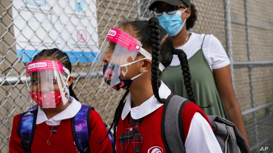 Students wear protective masks as they arrive for classes at the Immaculate Conception School while observing COVID-19…