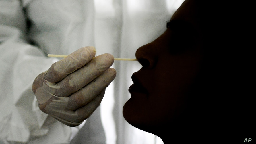 A doctor takes a nasal swab sample to test for COVID-19 at the Cocodrilos Sports Park in Caracas, Venezuela, Saturday, Sept. 19…