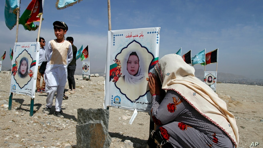 An Afghan woman cries next to the grave of her daughter, adorned with her picture, on the outskirts of Kabul, Afghanistan,…