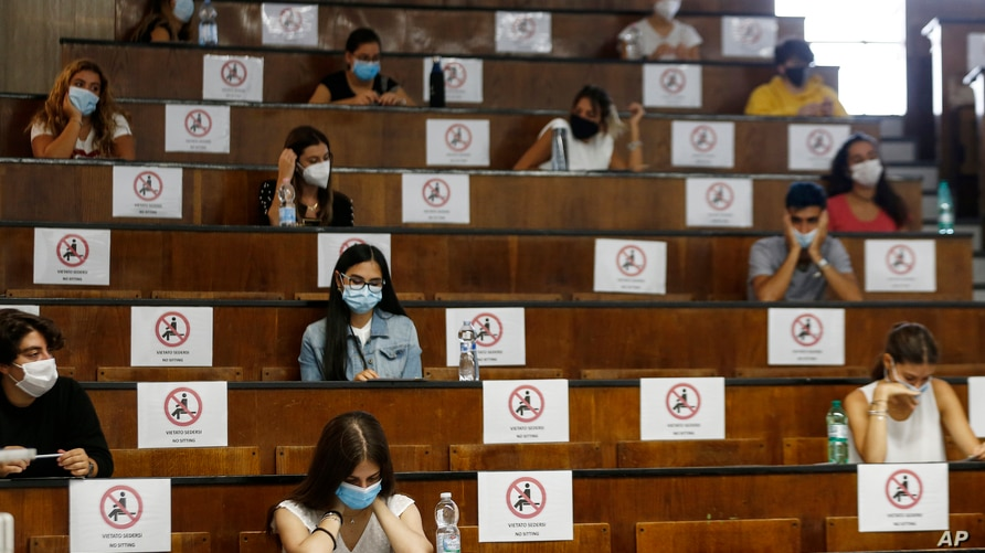 Students sit at a distance as a precaution against COVID-19, as they undergo an aptitude test to access the University of…