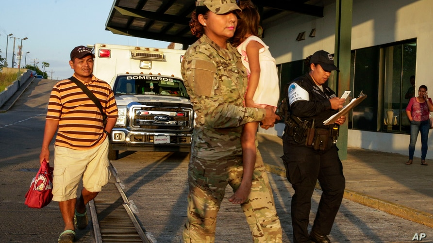 Jose Gonzalez, left, follows his 5-year-old daughter, carried by a police officer, as they leave a hospital in Santiago, Panama…