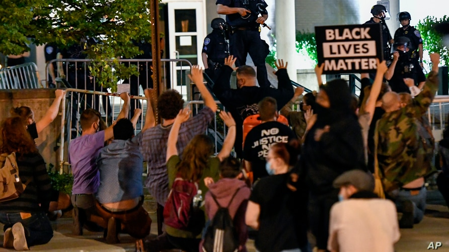 Protesters kneel in front of police officers outside the Public Safety Building in Rochester, N.Y., Thursday, Sept. 3, 2020…