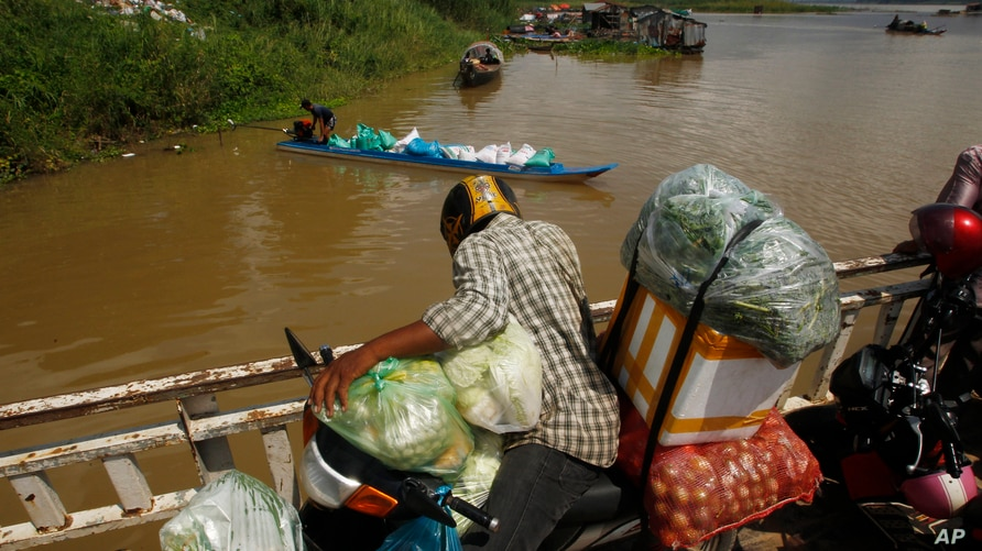 A vendor, foreground, stands on a ferry together with his goods before crossing the Mekong river in Dei Edth village at the…