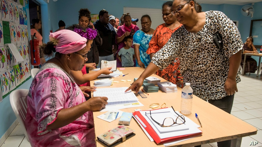 A woman points to a voting notebook before voting in Noumea, New Caledonia, Sunday, Oct.4, 2020. Voters in New Caledonia, a…
