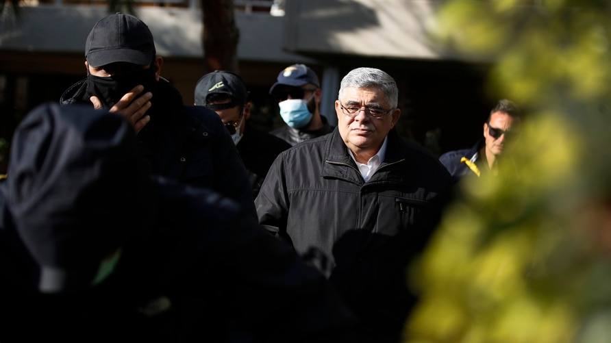 Golden Dawn party leader Nikos Michaloliakos, center, leaves his residence in Athens, Thursday, Oct. 22, 2020.A court has…