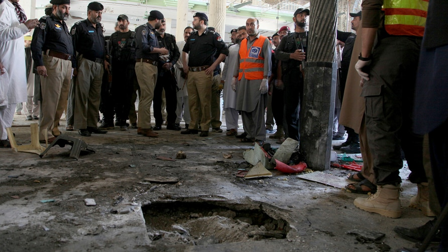 Police officers examine the site of bomb explosion in an Islamic seminary in Peshawar, Pakistan, Tuesday, Oct. 27, 2020. A…
