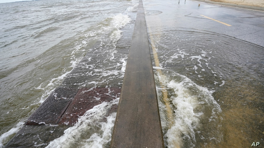 Waters from the Gulf of Mexico poor onto a local road, Monday, Sept. 14, 2020, in Waveland, Miss. Hurricane Sally, one of a…