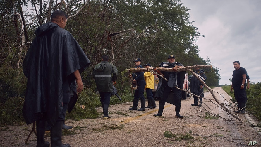 Police clear debris from a road after the passing of Hurricane Delta in Tizimin, Mexico, Wednesday, Oct. 7, 2020. Hurricane…