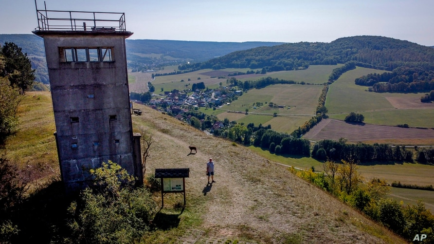 A former East German watch tower stands on a hill high above the former border area between East and West Germany in Unterweid,…