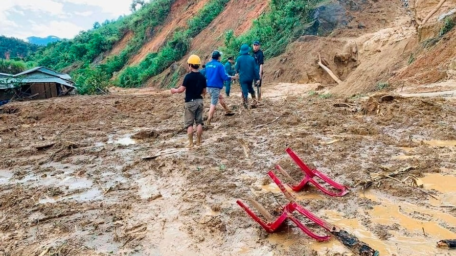 Villagers wade through mud after a landslide swamps a village in Phuoc Loc district, Quang Nam province, Vietnam Thursday, Oct…