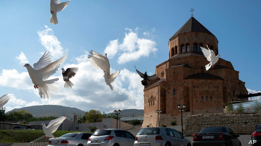 Pigeons fly near Holy Mother of God Cathedral in Stepanakert during a military conflict in the separatist region of Nagorno…