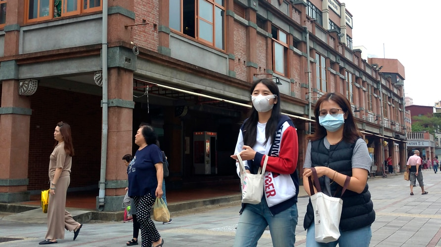 People wearing face masks to help curb the spread of the coronavirus walk on a street in Taipei, Taiwan, Monday, Oct. 19, 2020…