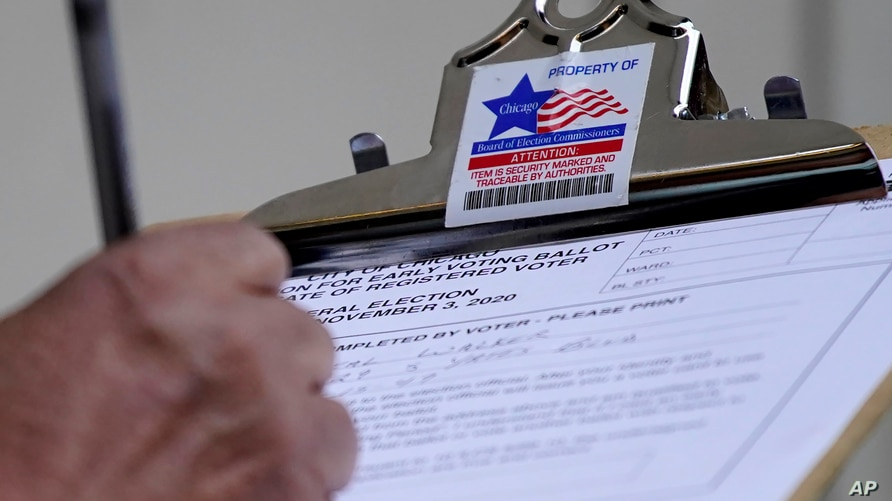 A man fills out voter registration card outside the Loop Super Site in downtown Chicago, Sunday, Oct. 11, 2020. It is the only…