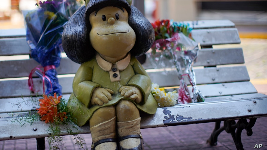 Flower bouquets flank a statue of the comic strip character Mafalda created by Argentine cartoonist Joaquin Salvador Lavado,…