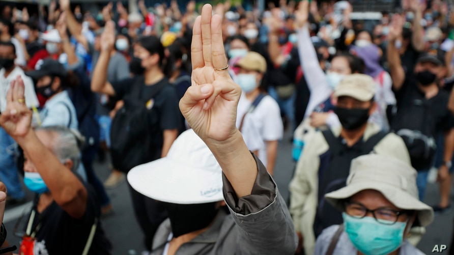Anti-government protesters raise a three-fingered salute, a symbol of resistance, as they march from Democracy Monument to…