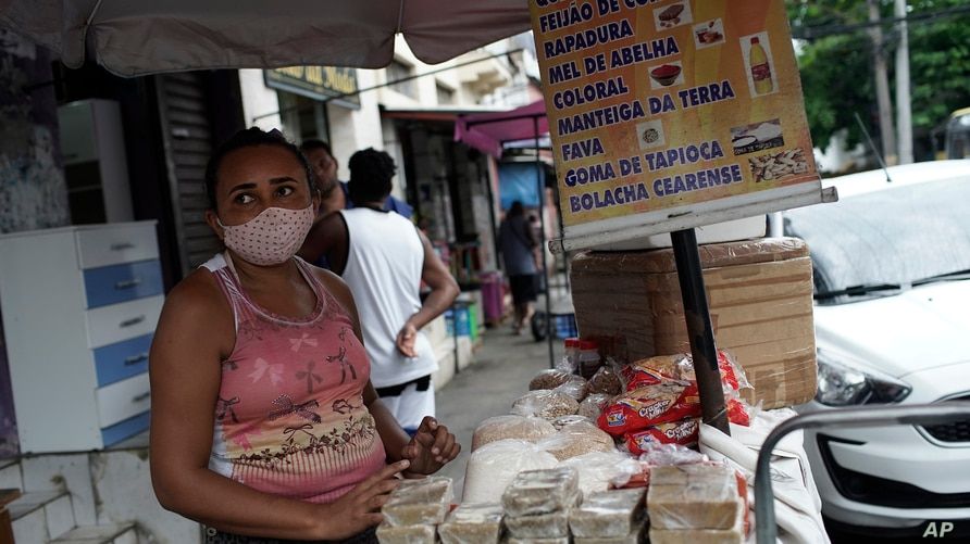 A street vendor wearing a mask amid COVID-19 sells cheese, beans, and sweets in Rio de Janeiro, Brazil, Friday, Oct. 9, 2020…