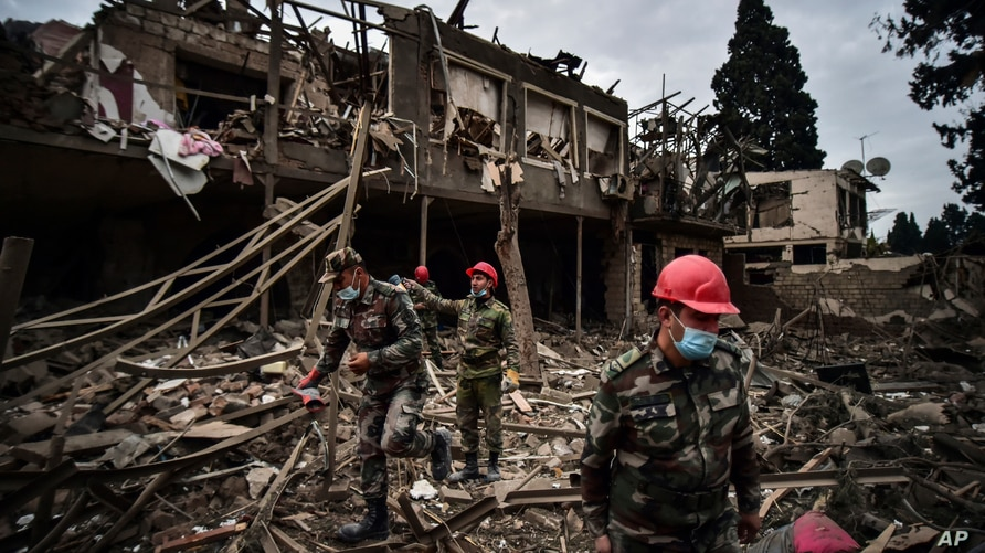 Azerbaijani soldiers and firefighters search for survivors after rocket fire overnight by Armenian forces, early Sunday, Oct…