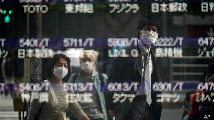 People are reflected on a blank electronic stock board supposedly showing Japan's Nikkei 225 index at a securities firm…