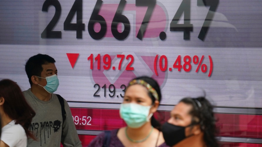 People wearing face masks walk past a bank's electronic board showing the Hong Kong share index in Hong Kong, Wednesday, Oct…