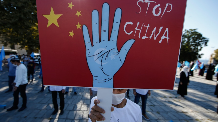 A protester from the Uighur community living in Turkey, holds an anti-China placard during a protest in Istanbul, Thursday, Oct…