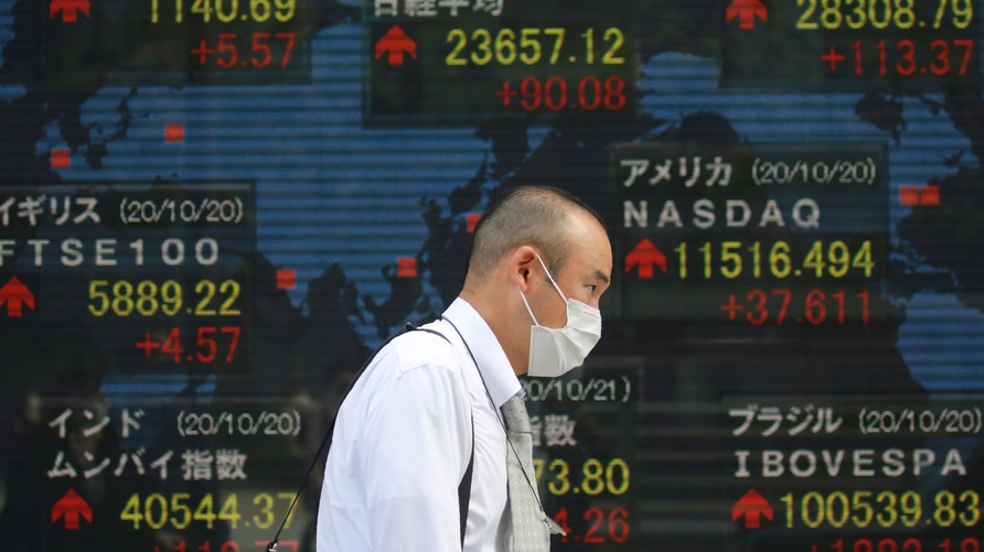 A man walks by an electronic stock board of a securities firm in Tokyo, Wednesday, Oct. 21, 2020. Asian shares mostly rose…